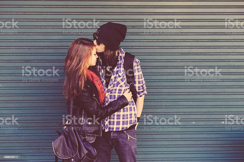 Boy kissing her girl on forehead stock photo