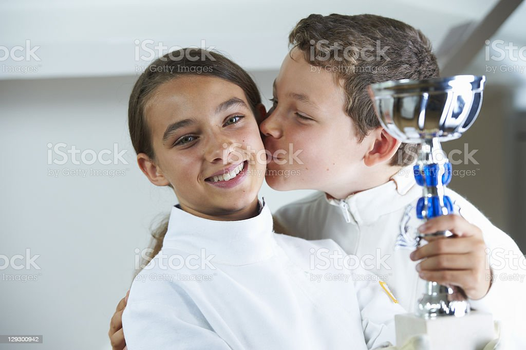 Boy kissing smiling fencing rival stock photo