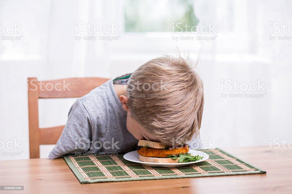 Boy landing face in food stock photo
