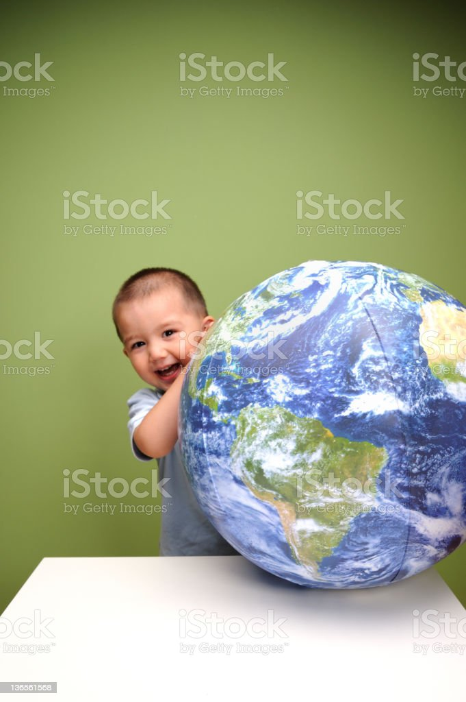 Boy laughing behind earth ball royalty-free stock photo