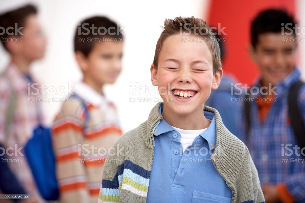 Boy (8-10) laughing, eyes closed, close-up stock photo