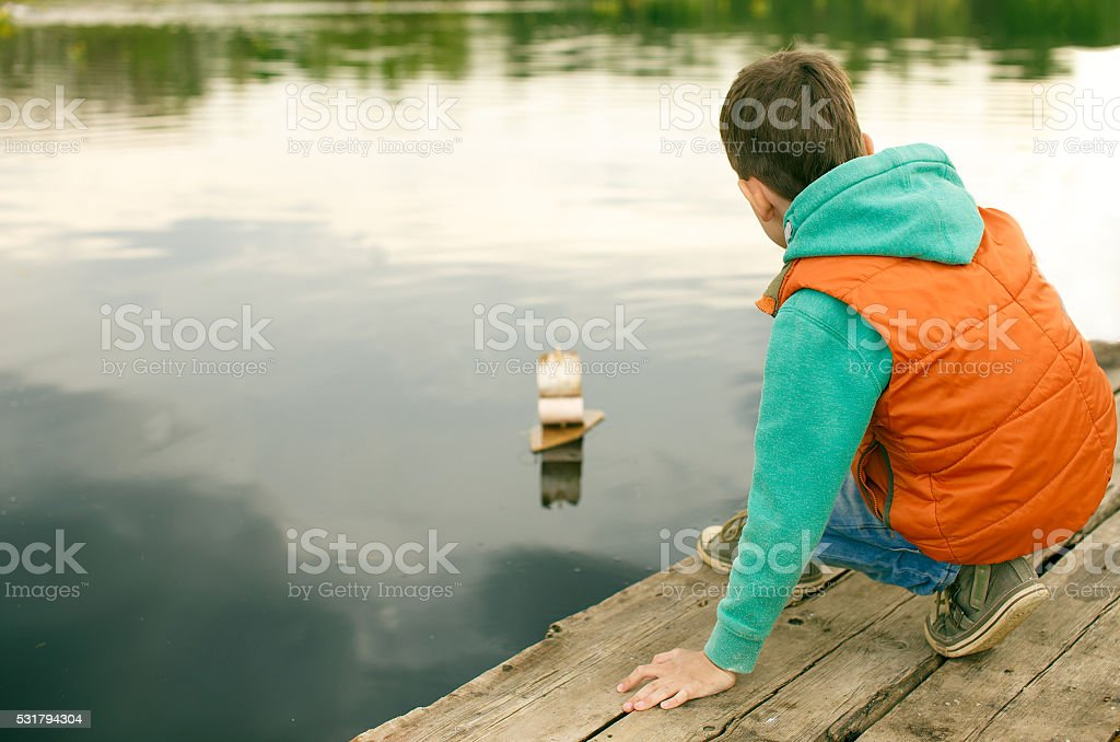 boy launches the toy wooden boat stock photo