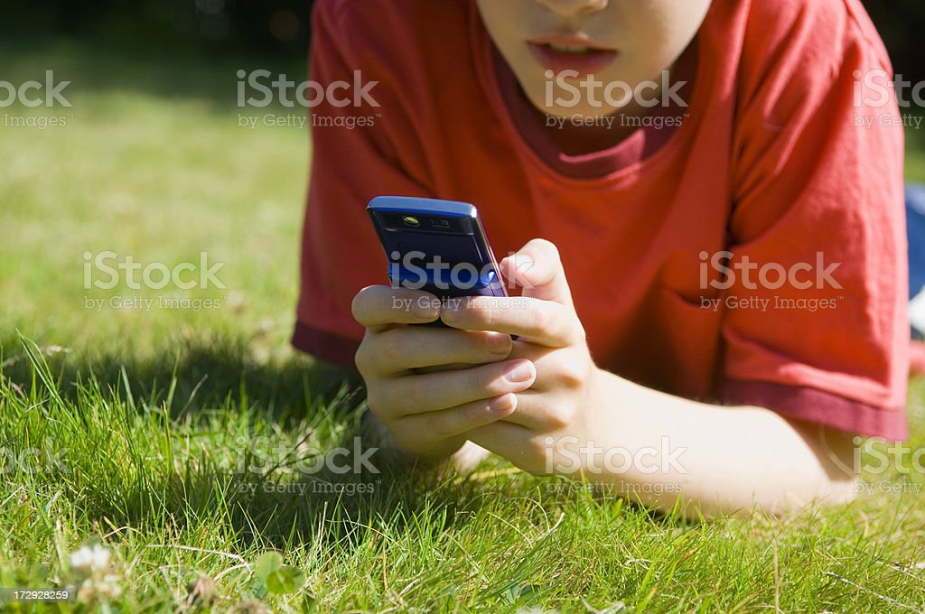Boy laying in the grass playing on a mobile phone royalty-free stock photo