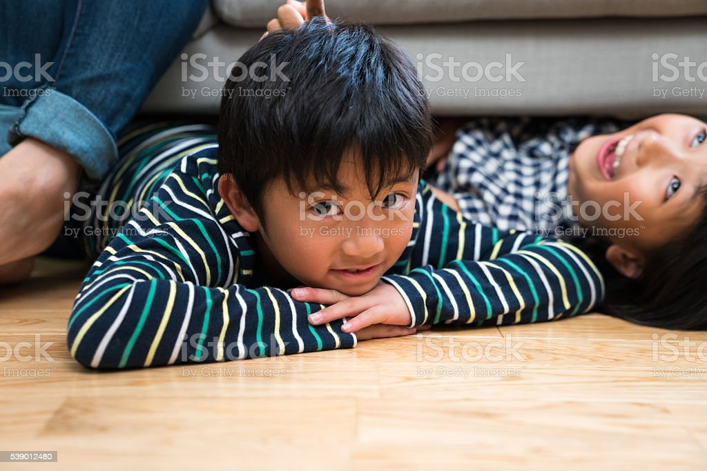 Boy laying on the floor with sister stock photo