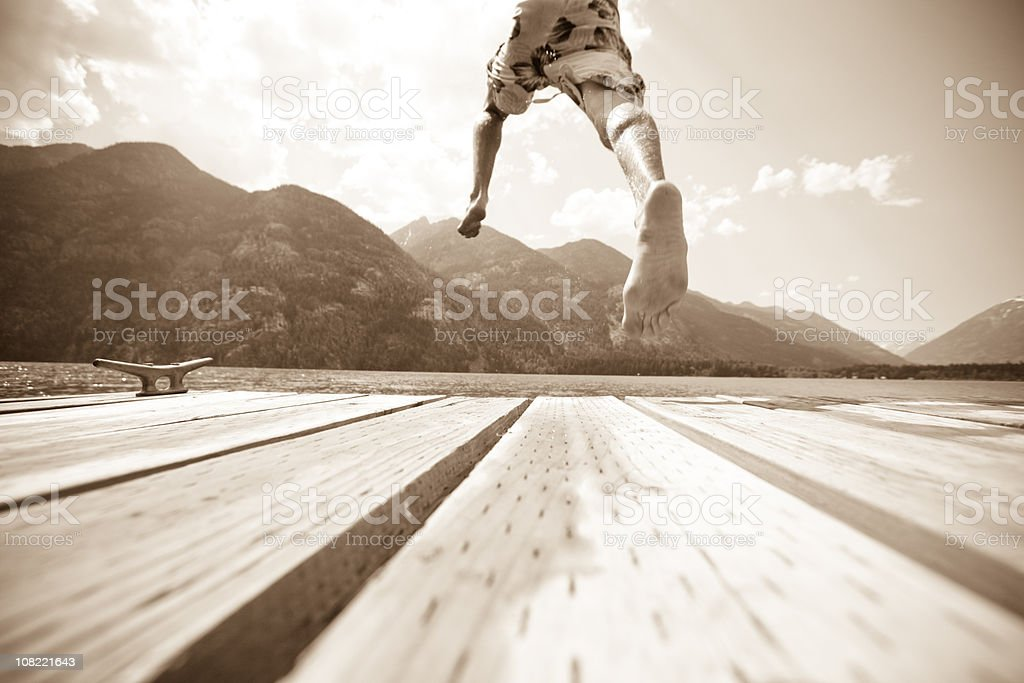 Boy leaping off a dock into cool refreshing water royalty-free stock photo
