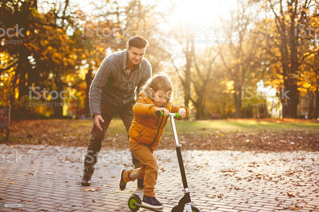 Boy learning how to ride scooter stock photo