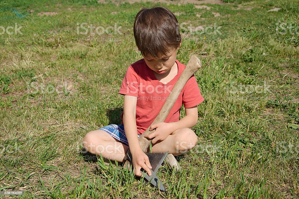 Boy learning in ax blade sharpening stock photo