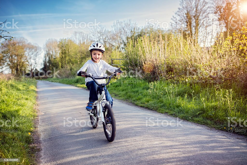 Boy learning to ride his bike stock photo