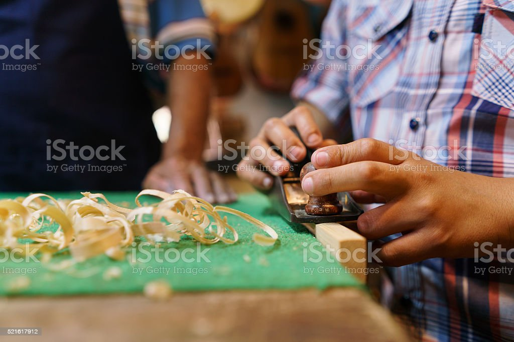 Boy Learns Crafting Wood In Lute Maker Shop stock photo
