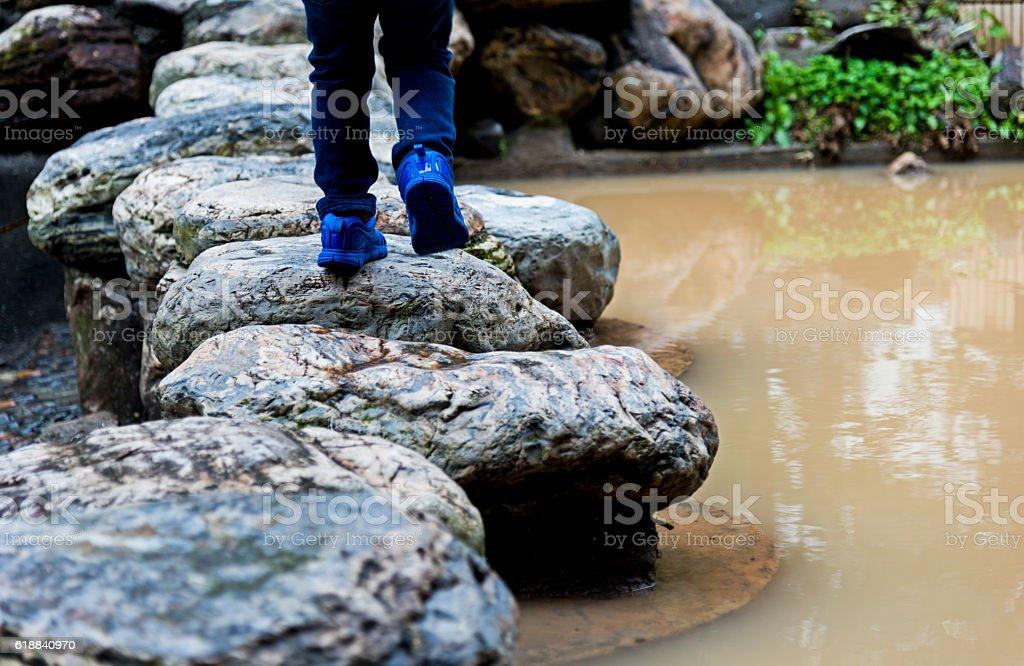 Boy legs crossing stepping stones stock photo