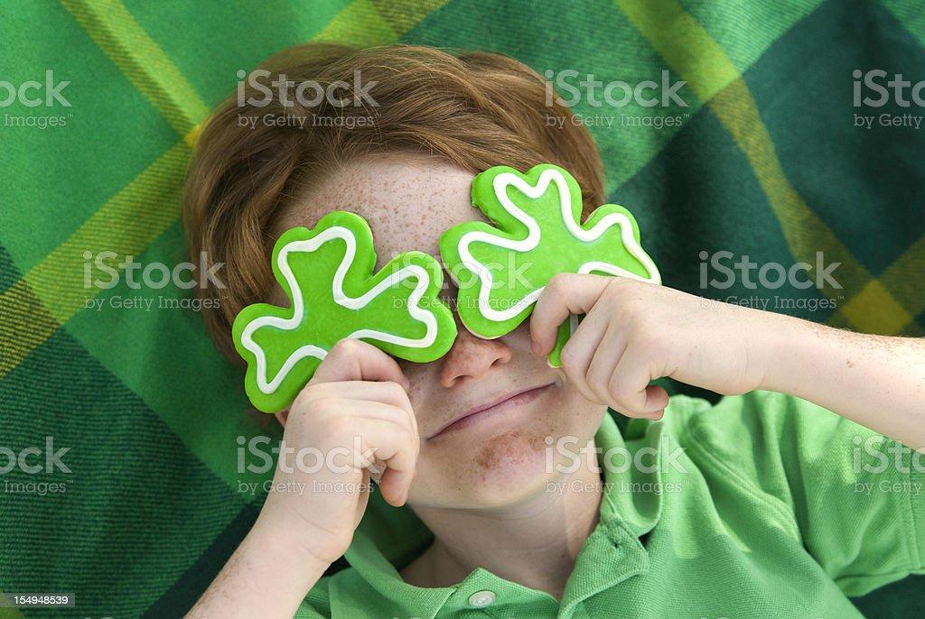 Boy Leprechaun, Smiling Irish Child & St. Patrick's Day Shamrock Cookies stock photo