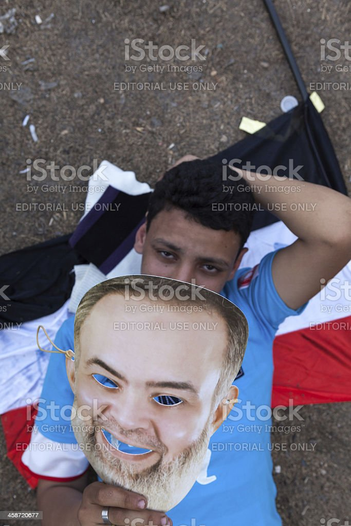 Boy lies on Egyptian flag during rally in Tahrir stock photo