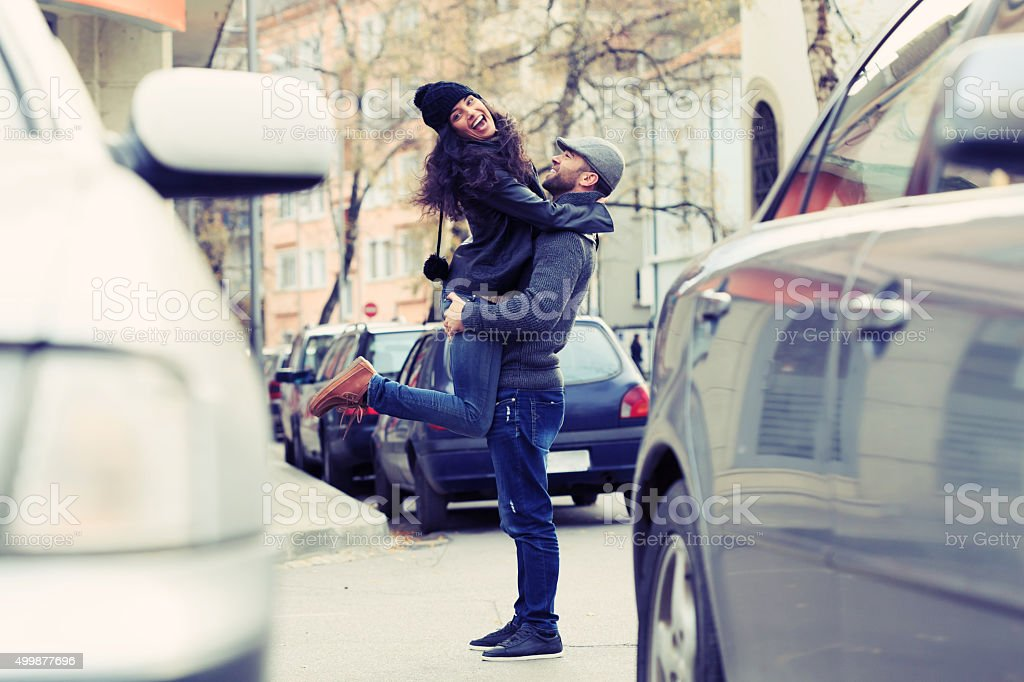 Boy lif a girl head back between two cars stock photo
