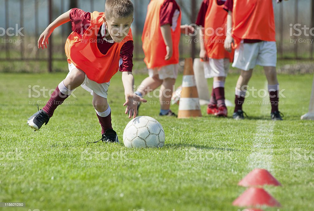 Boy lines up soccer ball with hand ready to play stock photo