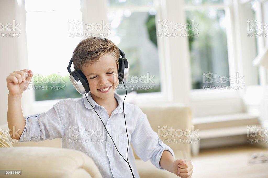 Boy (10-11) listening music through headphones and dancing royalty-free stock photo