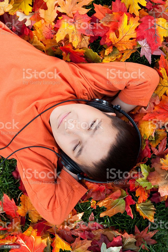 Boy listening to music on autumn leaves royalty-free stock photo