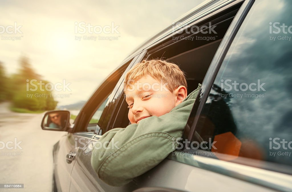 Boy look out from the car window stock photo