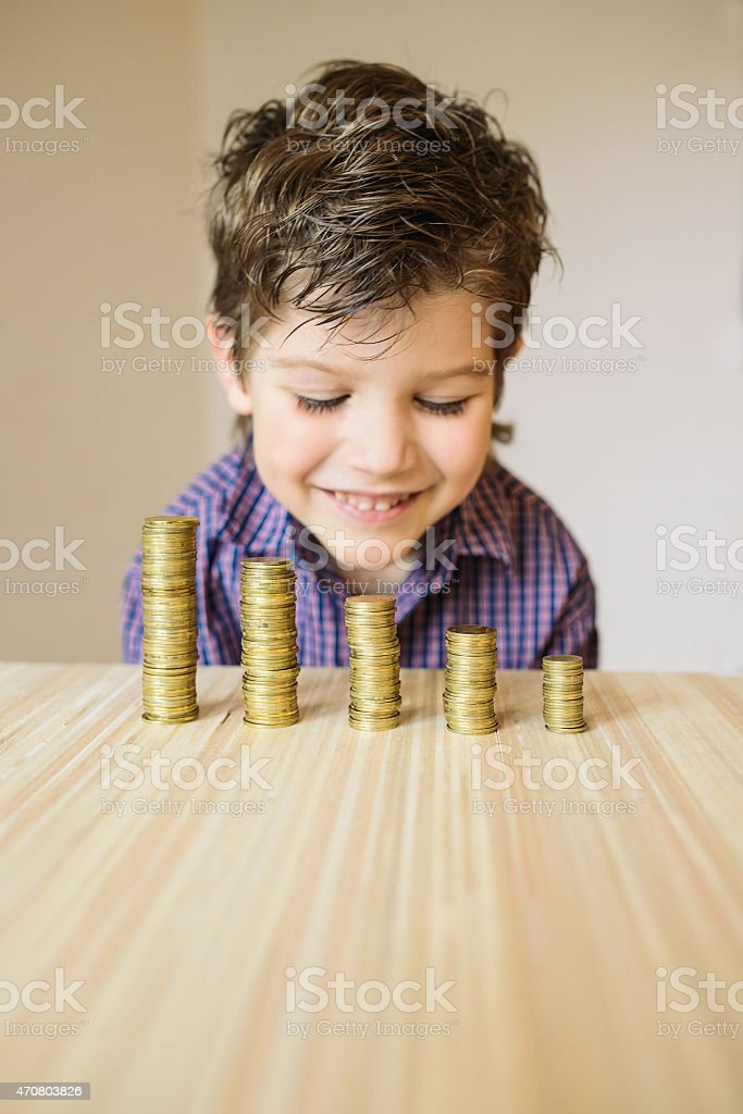 Boy looking at coins on a table stock photo
