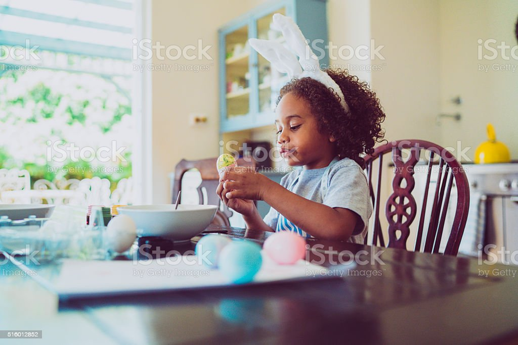 Boy looking at coloured Easter egg stock photo