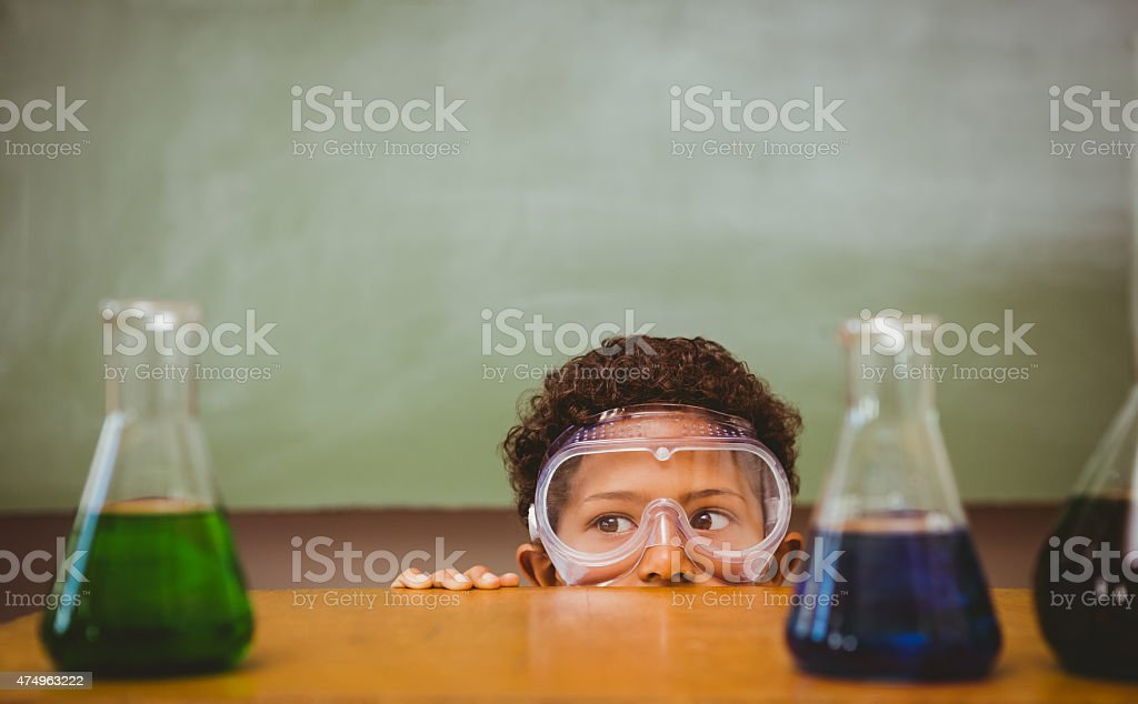 Boy looking at conical flasks in classroom stock photo