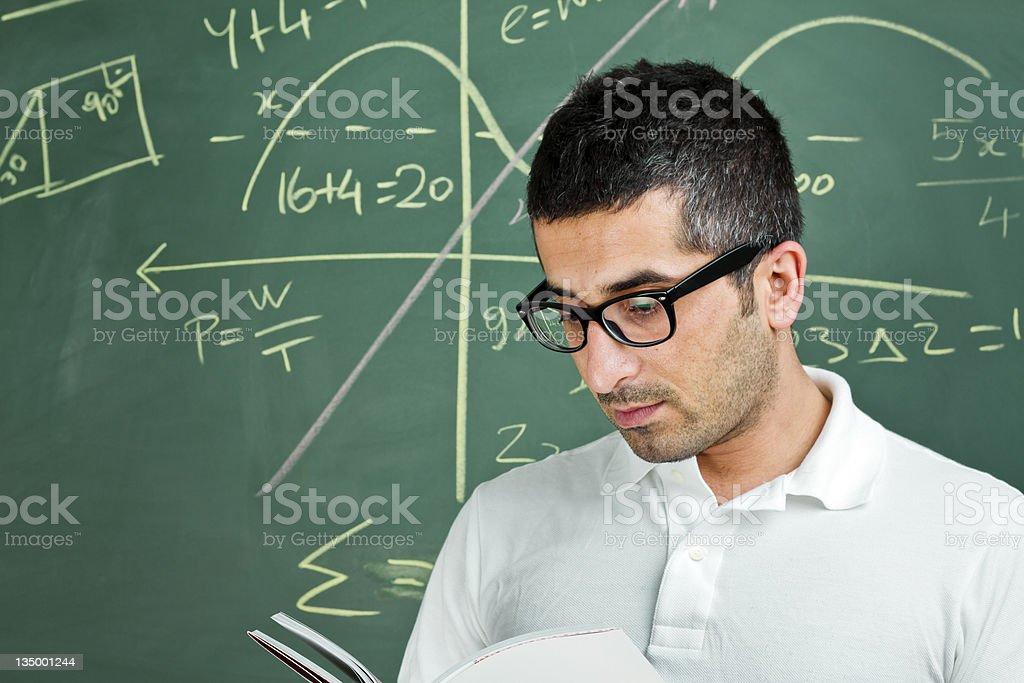 Boy looking at math problem on blackboard royalty-free stock photo