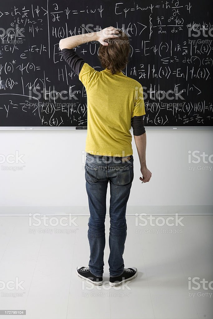Boy looking at math problem on blackboard stock photo