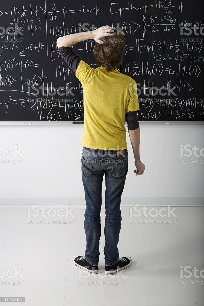 Boy looking at math problem on blackboard stock photo