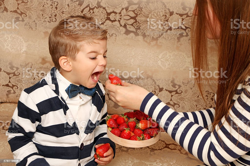 boy looking at strawberries and wants to bite it stock photo
