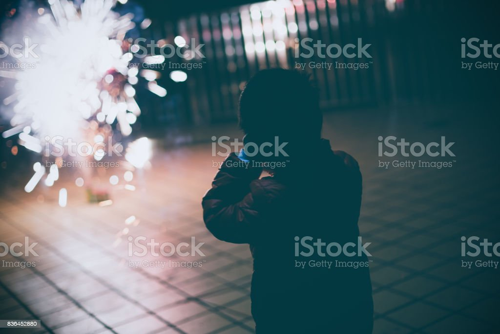 Boy looking fireworks with hands covering ears stock photo