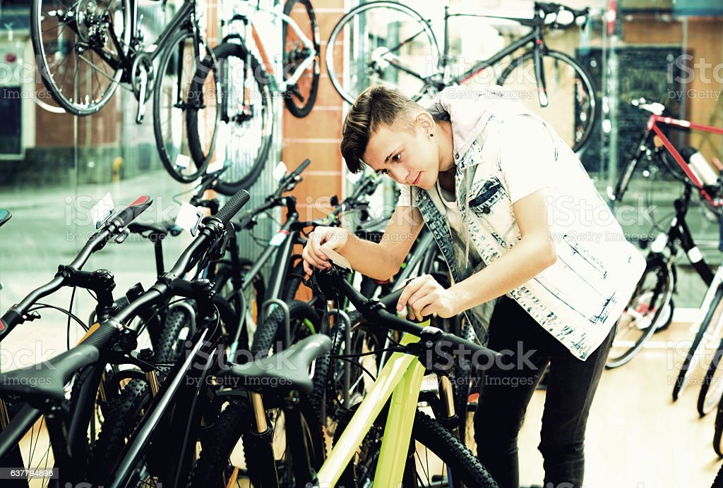 Boy looking for and trying new racing bicycle stock photo