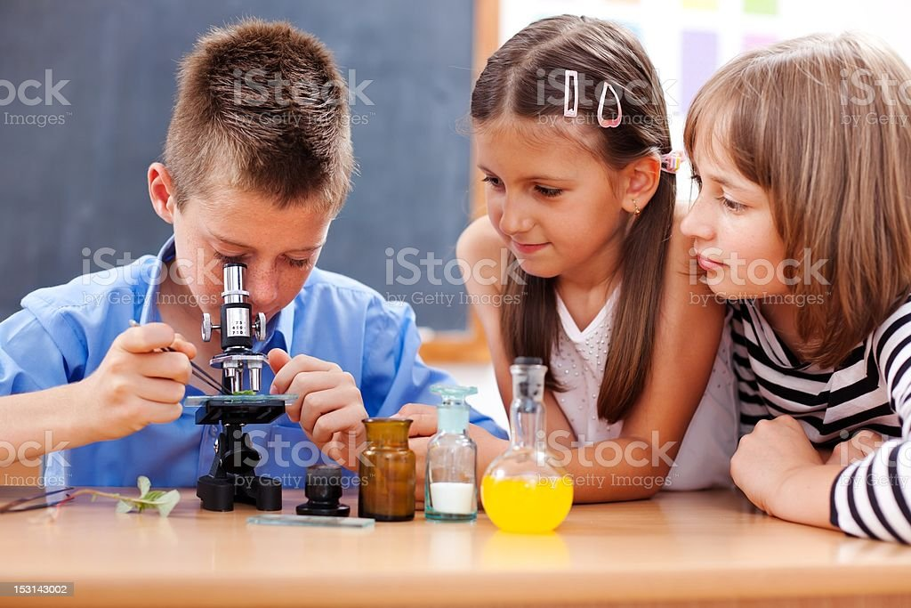 Boy looking into microscope stock photo
