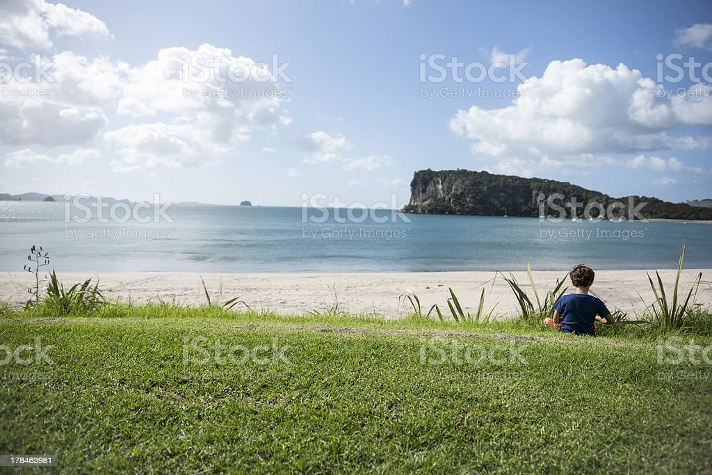 Boy looking out over bay. stock photo