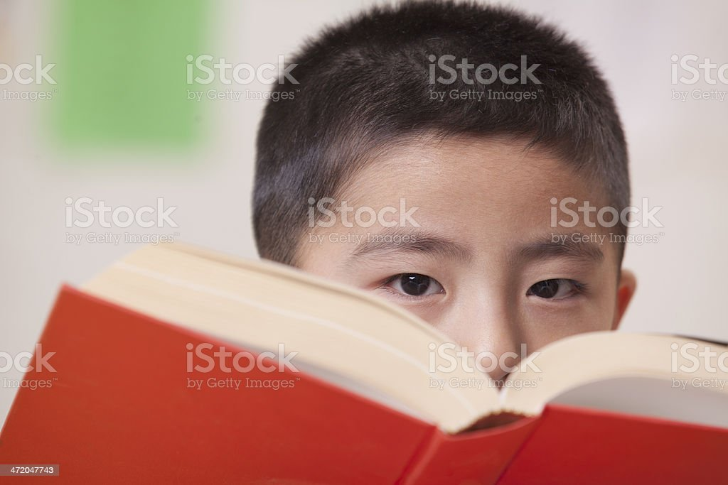 Boy Looking Over Book He's Reading stock photo