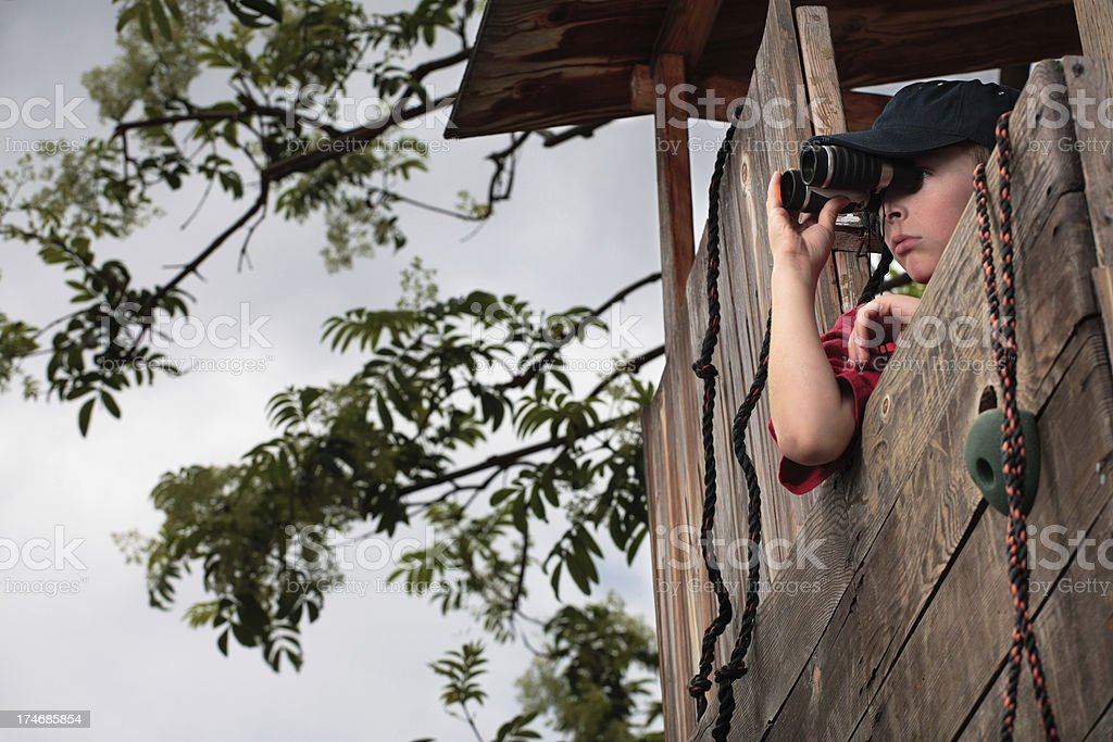 Boy looking through binoculars from fort. royalty-free stock photo