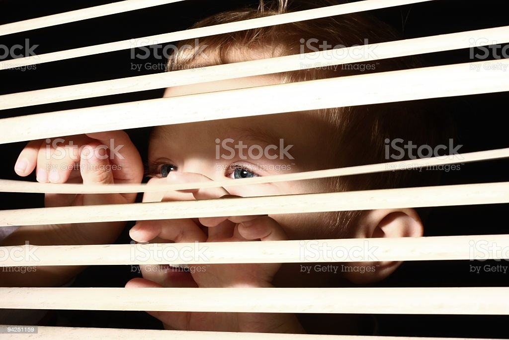Boy looking through blinds royalty-free stock photo