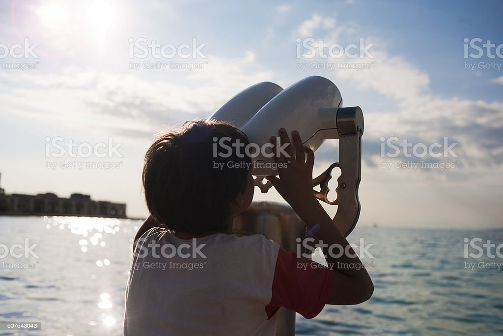 Boy looking through coin operated binoculars royalty-free stock photo