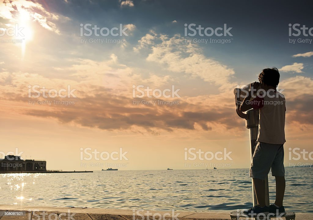 Boy looking through coin operated binoculars stock photo