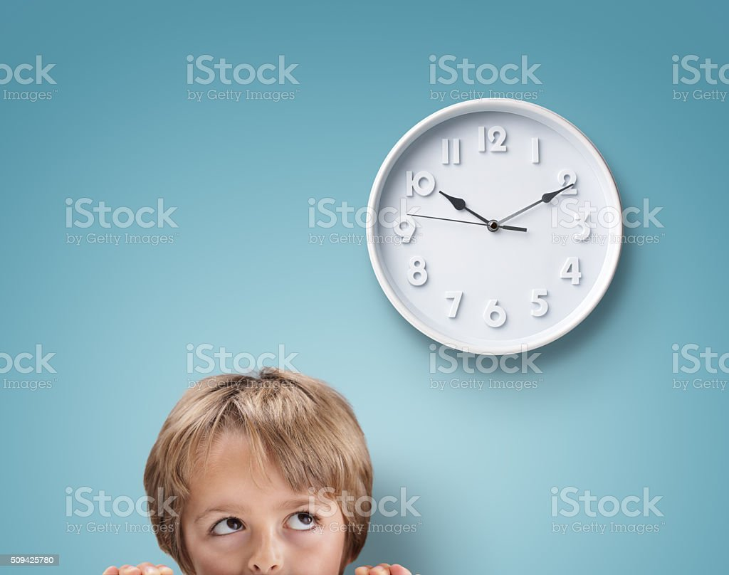 Boy looking up at a clock stock photo