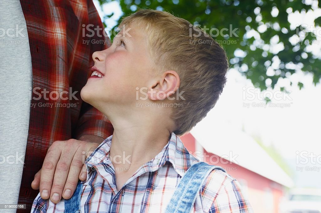 Boy looking up to father stock photo