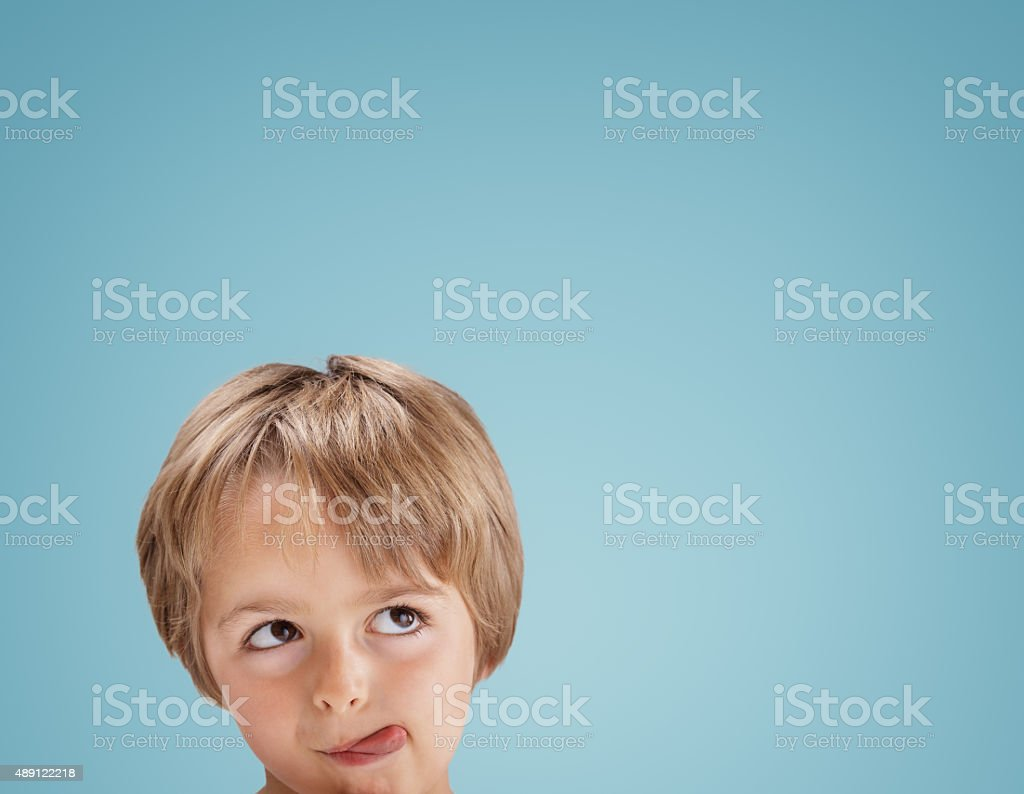 Boy looking up with tongue out licking his lips stock photo