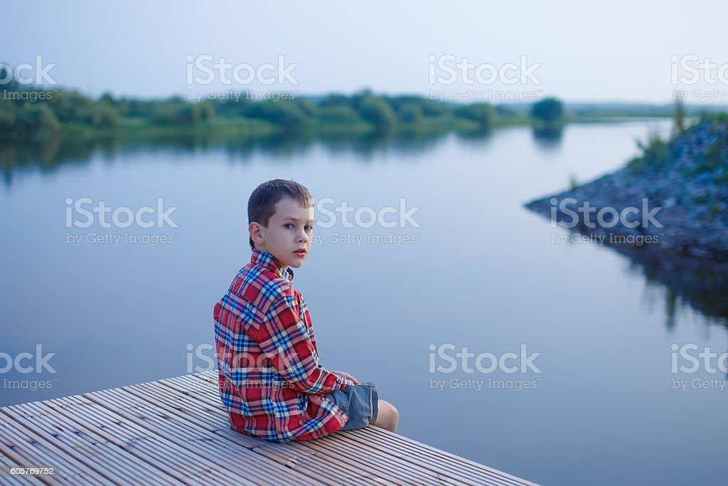 boy looks cautiously sitting near the water stock photo