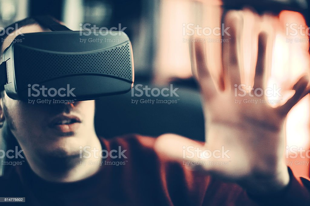 Boy looks fascinated into Virtual Reality Headset stock photo
