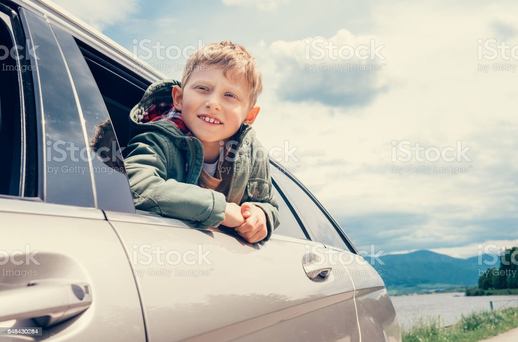 Boy looks out from car window stock photo