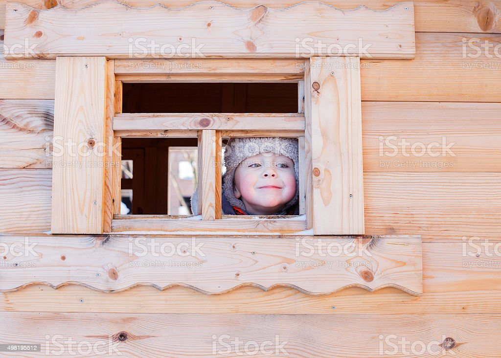 boy looks out the window of a wooden house stock photo