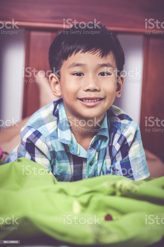 Boy lying barefoot on bed in bedroom. Happy child smiling. stock photo
