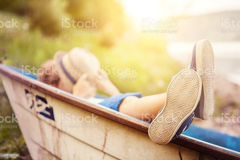 Boy lying in boat on lake coast close up image stock photo