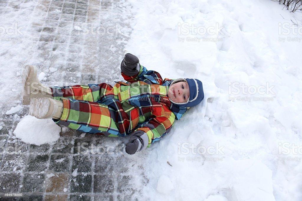 Boy lying in the snow stock photo