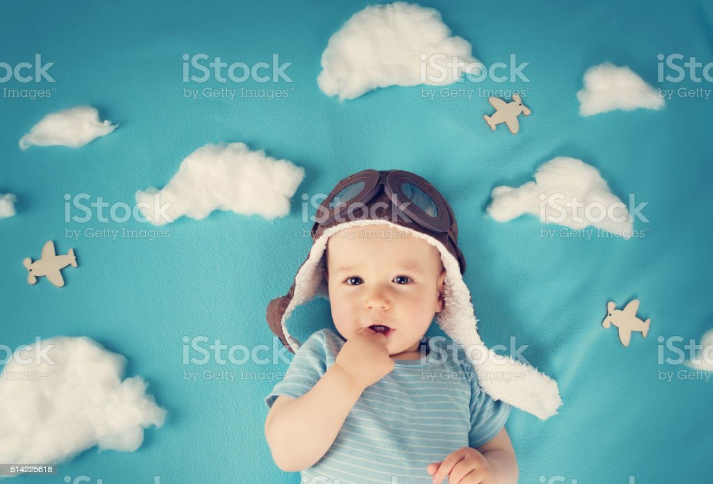 boy lying on blanket with white clouds stock photo