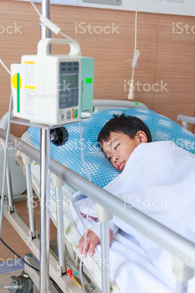 Boy lying on sickbed with infusion pump intravenous IV drip stock photo