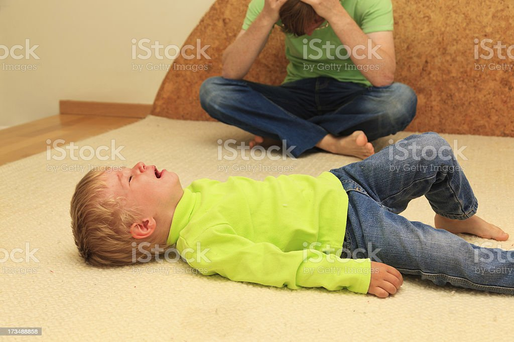 Boy lying on the floor crying in front of his upset father royalty-free stock photo